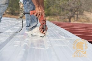 A Roofer Fastens a Panel With a Drill.
